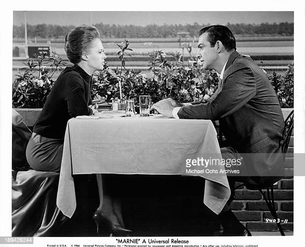 Tippi Hedren and Sean Connery at race track table in a scene from the film 'Marnie' 1964