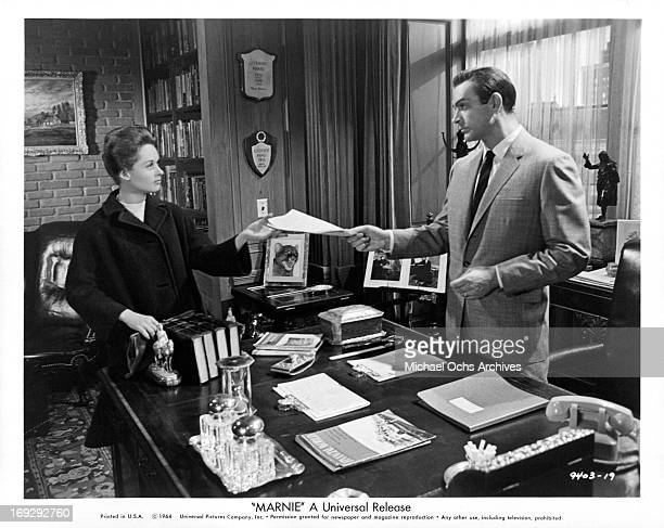 Tippi Hedren is handed a work assignment by Sean Connery in a scene from the film 'Marnie' 1964