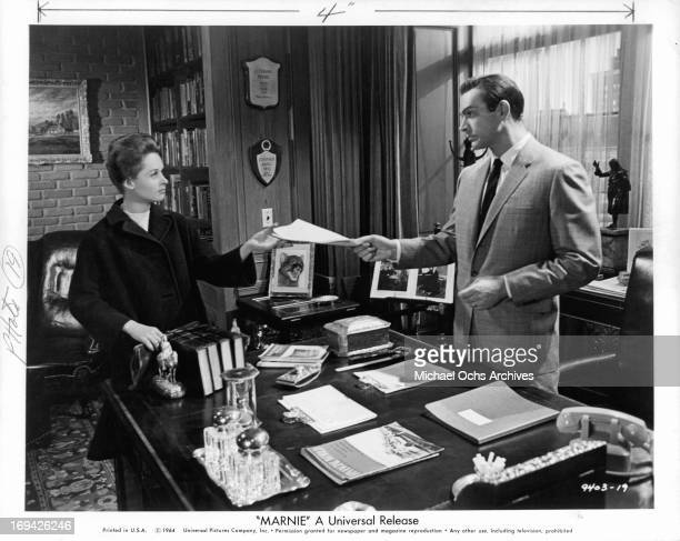 Tippi Hedren is handed documents from Sean Connery in a scene from the film 'Marnie' 1964
