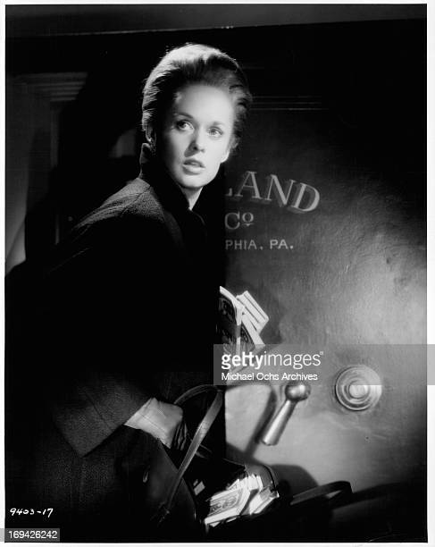 Tippi Hedren standing at company safe in a scene from the film 'Marnie' 1964
