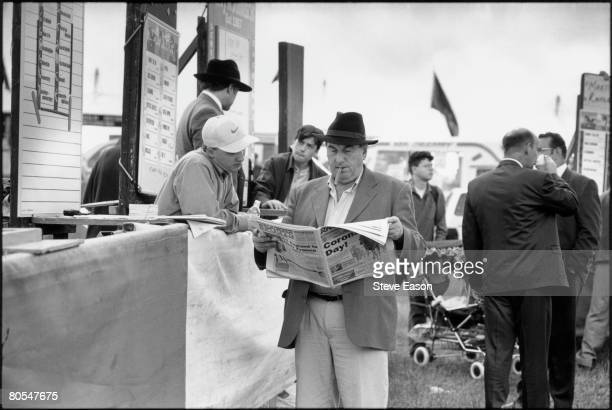 Tipster reading a newspaper at a bookmaker's stall at Epsom racecourse on Derby Day, 7th June 1997.