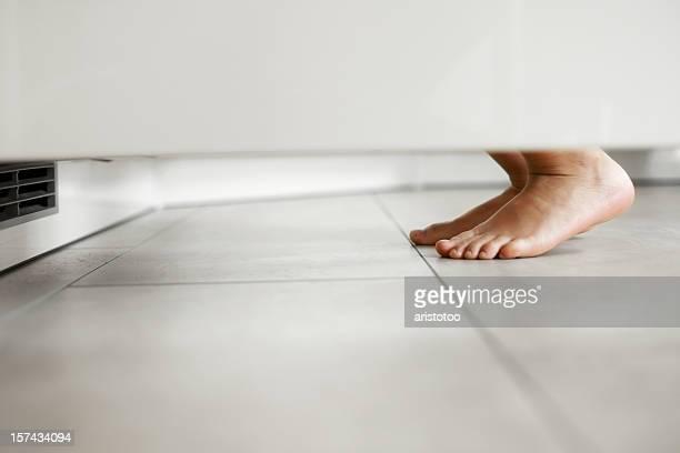 Auf den Zehenspitzen kleines Mädchen schaut in den Kühlschrank.