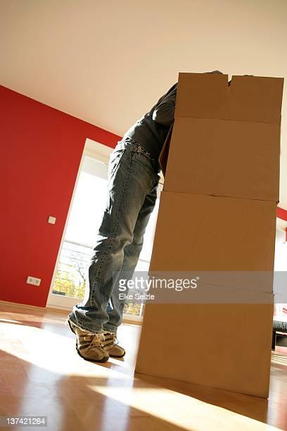 Tiptoeing man bending over boxes in empty apartmen