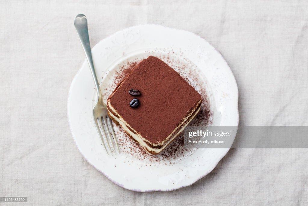 Tiramisu, traditional Italian dessert on a white plate. Copy space. Top view. : Stock Photo