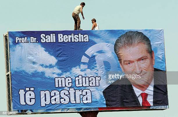 Albanian workers adjust a electoral poster of the leader of the Albanian Democratic Party former Albanian President Sali Berisha near the city of...
