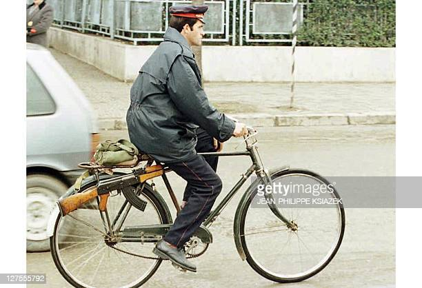 A Tirana policeman carrying a Kalashnikov on his bicycle rides 03 April through the streets of the capital where Albanian security forces deployed...