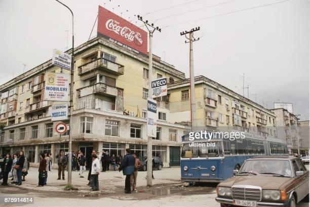 Straßenszene An einer Straßenkreuzung warten Menschen auf den Bus ein PKW der Marke Mercedes fährt vorbei An Strom und Lichtmasten sind Werbetafeln...