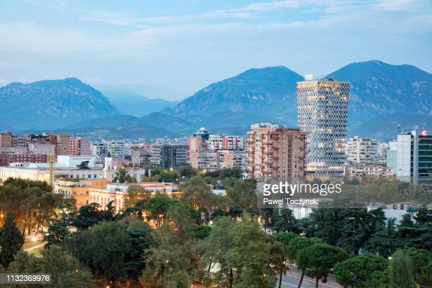 tirana's downtown area with the tallest building in the city - the plaza tirana at sunset (85m), albania, 2018 - socialism stock pictures, royalty-free photos & images