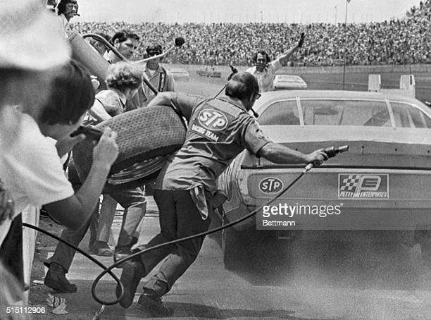 Tire and air hose in hand, a crewman rushes to Richard Petty's car 7/4 as Petty comes to a stop in a cloud of tire smoke. Petty got tires and...