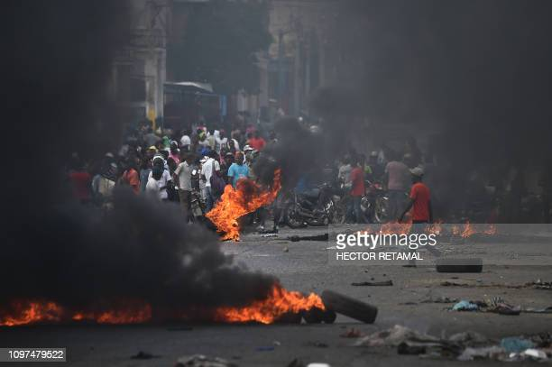 Tire barricades are set ablaze by demonstrators on the fourth day of protests in Port-au-Prince, February 10 against Haitian President Jovenel Moise...