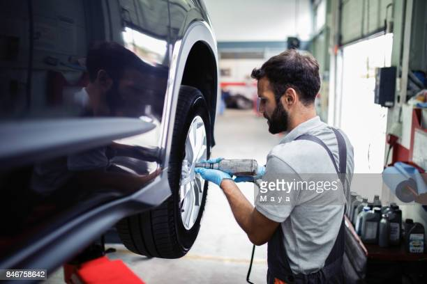 tire changing at car service - auto repair shop stock pictures, royalty-free photos & images