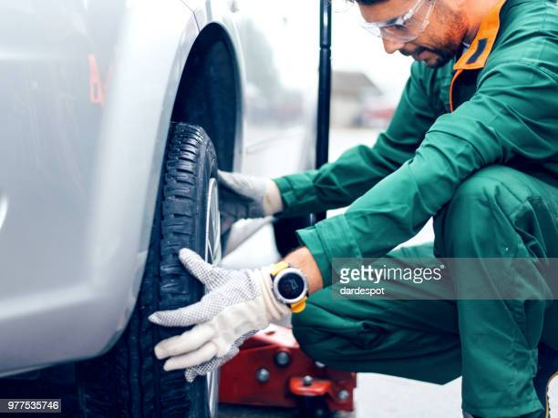 tire changing at car service - flat tire stock pictures, royalty-free photos & images