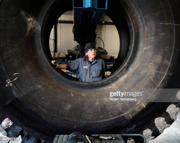 A tire mechanic repairs a 12foot diameter tire at the Big Horn Tire Shop in Gillette Wyoming June 15 2006 Giant tires are used on earth moving...