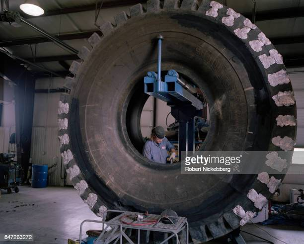 Tire mechanic repairs a 12-foot diameter tire at the Big Horn Tire Shop in Gillette, Wyoming, June 15, 2006. Giant tires are used on earth moving...