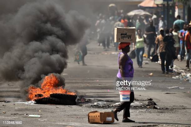 TOPSHOT A tire placed by a small group of demonstrators burns on a street in the commune of Petion Ville in the Haitan capital PortauPrince on...