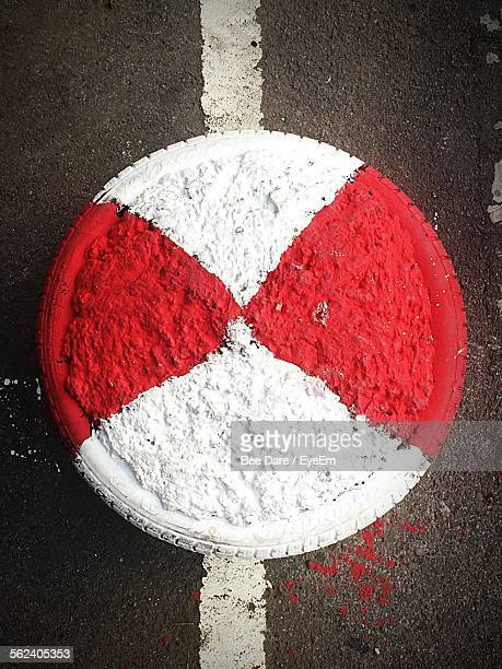 Tire Positioned On Center Of Road Between Diving Line Filled In Two Colors Red And White Chalk Colors