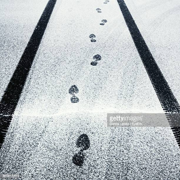 tire tracks and footprints in layer of snow on black street - track imprint stock photos and pictures