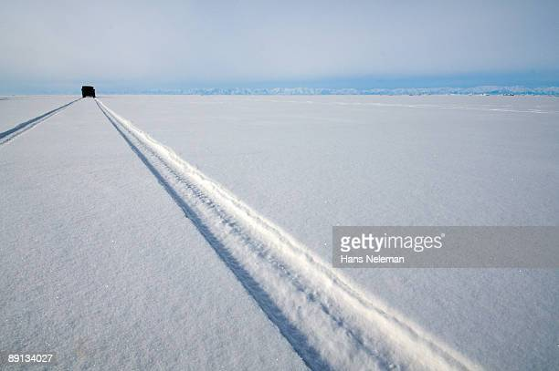 Tire tracks of a car on a snow covered road, Severobaykalsk, Russia