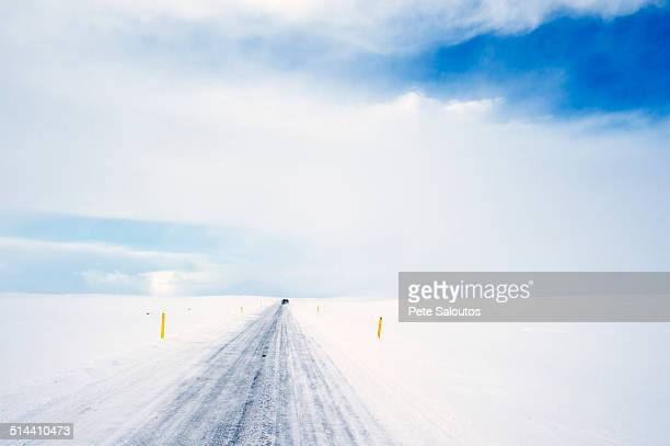 Tire tracks on rural road in snowy landscape