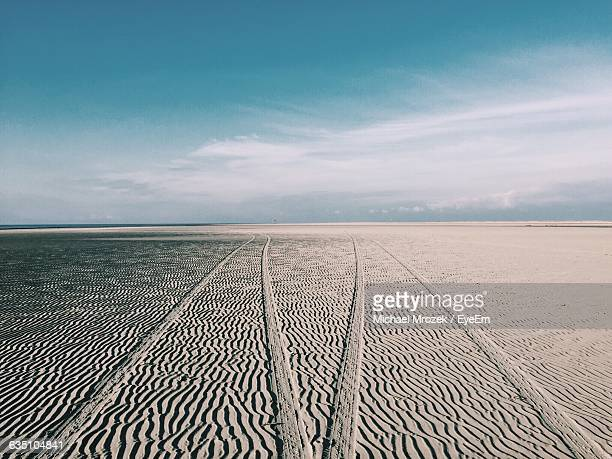Tire Tracks On Sand Pattern Against Sky At Beach