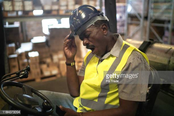 tired african mature forklift driver man - tired stock pictures, royalty-free photos & images