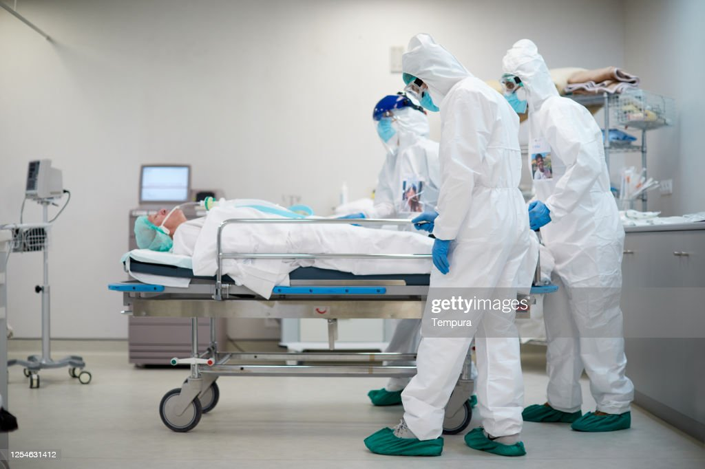 Tired and sad healthcare workers pushing a hospital gurney : Stock Photo