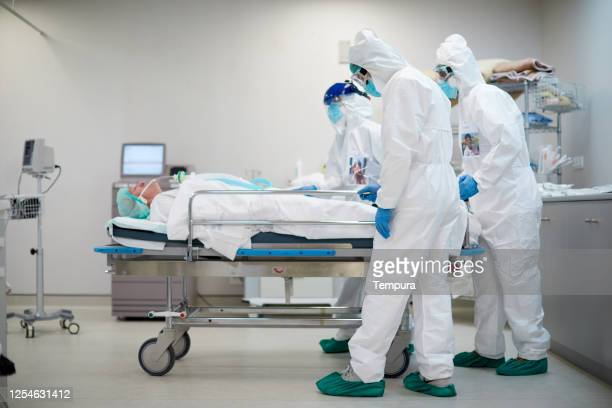 tired and sad healthcare workers pushing a hospital gurney - death stock pictures, royalty-free photos & images