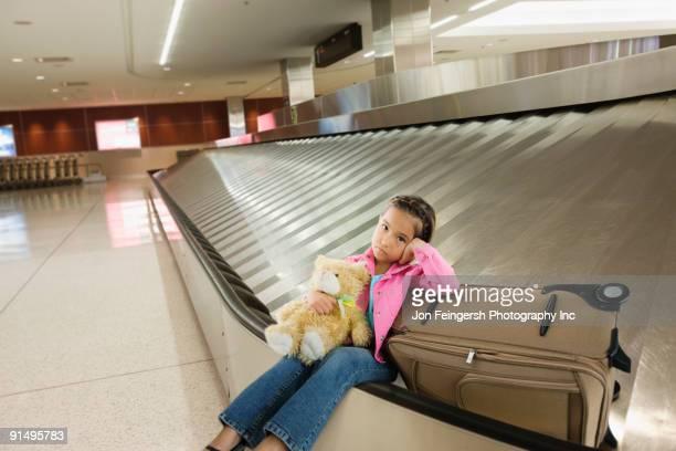 Tired Asian girl sitting on luggage carousel
