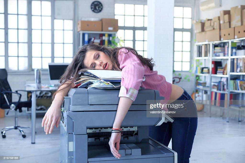 Cansado assistente de dormir em uma copiadora : Foto de stock