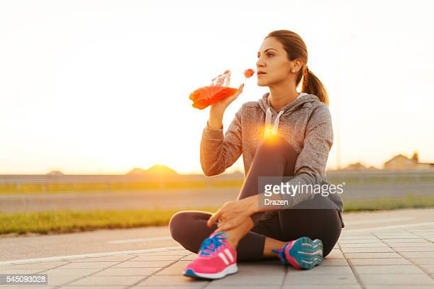 Tired athlete drinking energy drink after training in nature
