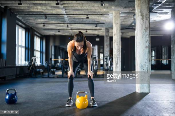 tired athlete standing with hands on knees in gym - crossfit stock pictures, royalty-free photos & images