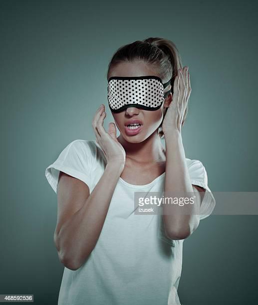 Erschöpft blonde Frau mit Maske auf Ihre Augen Schlafen