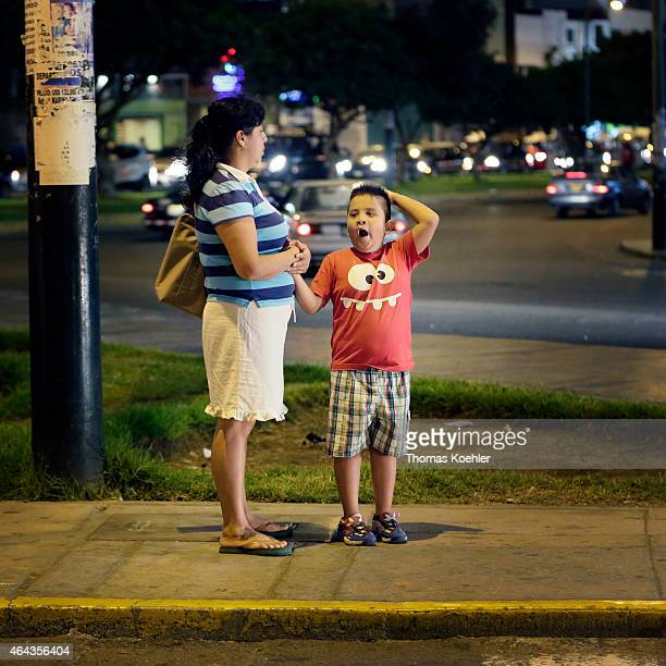Tired boy waiting with his mother for the bus on February 14 2015 in Lima Peru