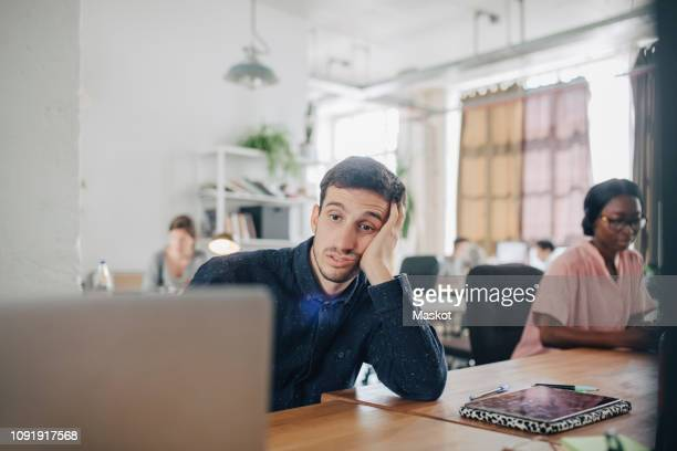 tired businessman looking at laptop while sitting at desk in creative office - boredom stock pictures, royalty-free photos & images