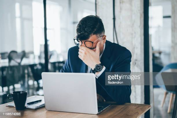 tired businessman - head in hands stock pictures, royalty-free photos & images