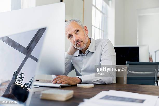 Tired businessman using computer at desk in office