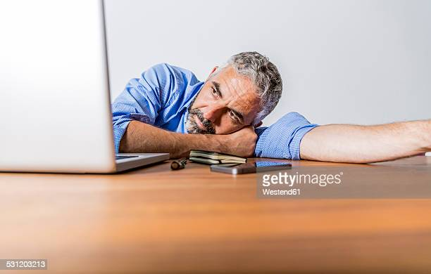 Tired businessman with laptop at home office
