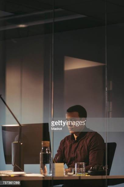 Tired businessman working at desk in dark office