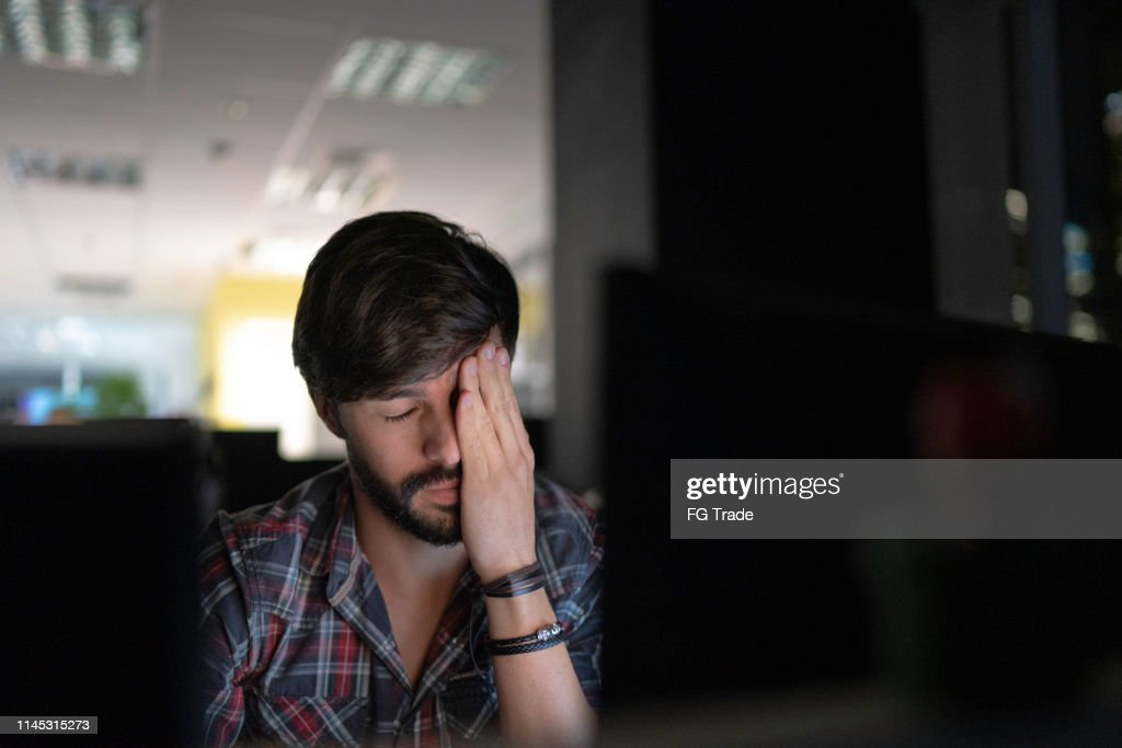 Tired businessman working late and rubbing eyes : Stock Photo