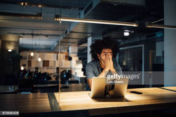 tired businessman working on laptop at desk - problema - fotografias e filmes do acervo