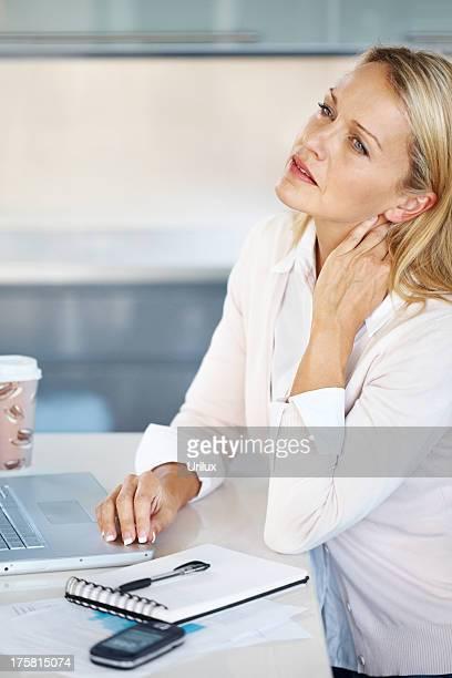 Cansado Mulher de negócios na sua secretária com dor no pescoço