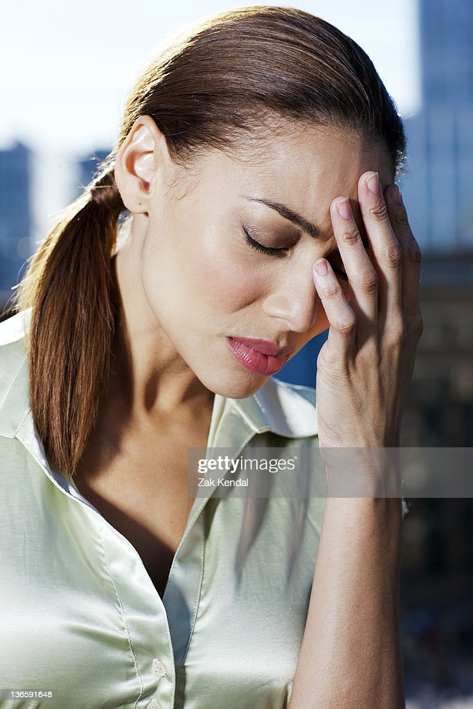 Tired businesswoman holding her head : Stock Photo