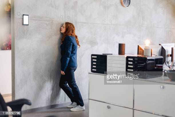 tired businesswoman leaning against a wall in office - dormir humour photos et images de collection