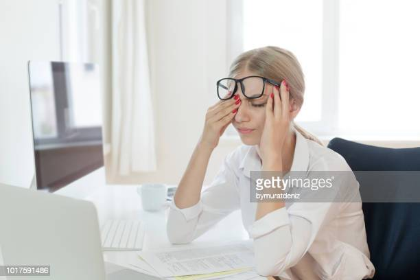 tired businesswoman rubbing eyes in office - jet lag stock pictures, royalty-free photos & images