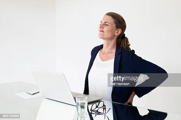 Tired businesswoman suffering backache while working at office desk