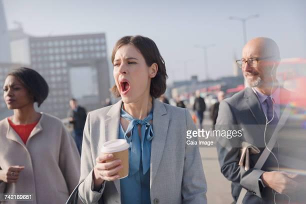 Tired businesswoman with coffee yawning on sunny morning urban pedestrian bridge