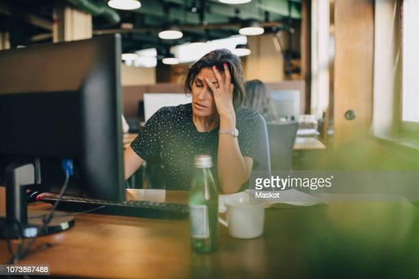 tired businesswoman with head in hand sitting at computer desk in office - werkgelegenheid en arbeid stockfoto's en -beelden