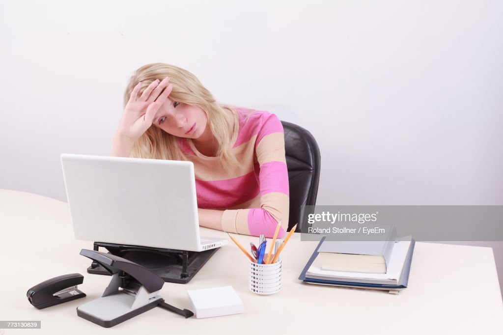 Tired Businesswoman Working On Laptop Against White Background : Stock Photo