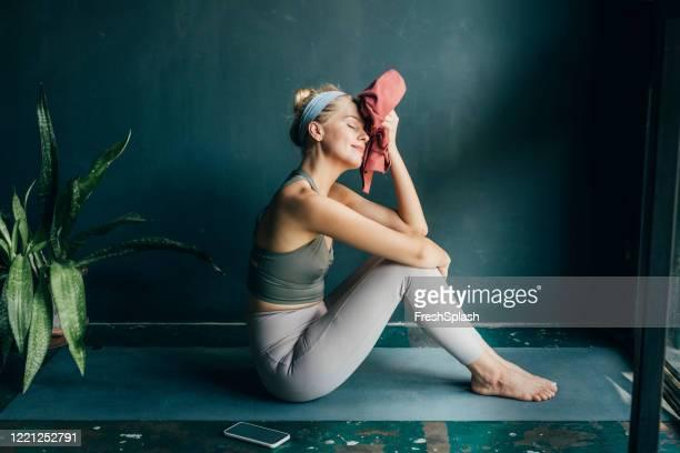 moe, maar gelukkig: fit blonde vrouw veegt haar gezicht met een handdoek na een home workout - trainen stockfoto's en -beelden