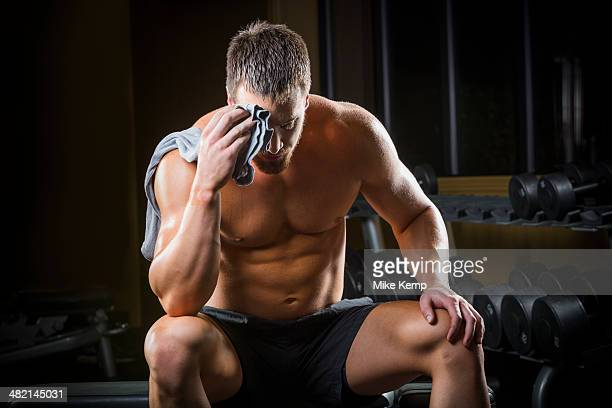 Tired Caucasian man wiping sweat off forehead in gym